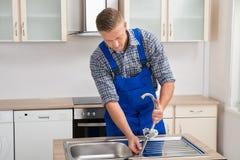 Repairman Installing Faucet Of Kitchen Sink Stock Photo