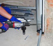 Repairman Installing Garage Door. Contractor Using Drill and Metal Anchor Bolt to Attach Plastic and Metal Profil Section Garage Door Panel to Wall Stock Photography