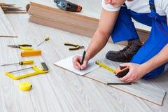Repairman kłaść laminat podłoga w domu zdjęcia stock