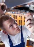 Repairman during kitchen hood reparation Stock Photography