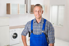 Repairman In The Kitchen. Photo Of Young Happy Repairman Standing In Kitchen Royalty Free Stock Image
