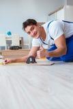 The repairman laying laminate flooring at home. Repairman laying laminate flooring at home royalty free stock photos
