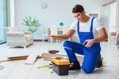 The repairman laying laminate flooring at home Royalty Free Stock Images