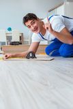 The repairman laying laminate flooring at home Stock Photos