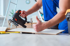 The repairman laying laminate flooring at home. Repairman laying laminate flooring at home stock photo