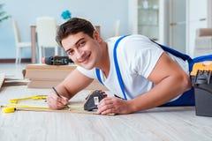 The repairman laying laminate flooring at home Stock Photography