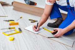 The repairman laying laminate flooring at home Stock Photos