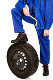 Repairman leg on a tire Stock Images