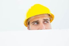 Repairman looking away while in front of billboard Royalty Free Stock Images