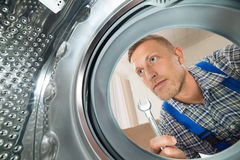 Repairman Looking Inside The Washing Machine Stock Photo
