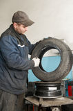 Repairman lubricating car tyre Royalty Free Stock Images