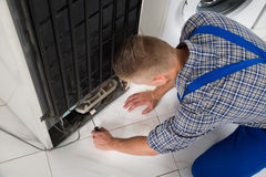 Repairman Making Refrigerator Appliance royaltyfri foto