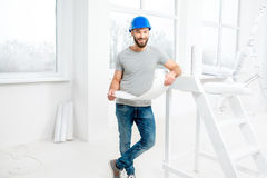 Repairman making repairs in the apartment. Handsome repairman or builder in helmet working with drawings on renovation of apartment interior Stock Photo