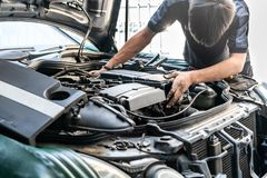 Repairman or mechanic during car repair investigate cause of problem mechanism or combustion system check automobile gasoline or. Diesel engine at garage royalty free stock image