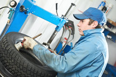 Repairman mechanic lubricating car tyre Royalty Free Stock Image