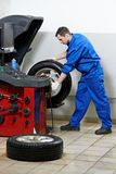 Repairman mechanic at wheel balancing Royalty Free Stock Photography
