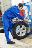 Repairman mechanic at wheel replacement royalty free stock photo