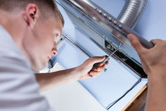 Repairman mending a kitchen extractor. Young handyman fixing a kitchen extractor with a screwdriver Stock Photography