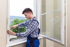 Repairman naprawiania okno Z śrubokrętem zdjęcia stock