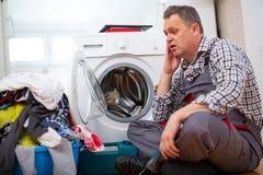 Repairman naprawiania płuczka W kuchni, Siedzi Obok Brudnej pralni fotografia royalty free