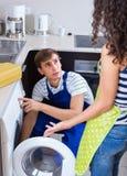 Repairman och klient nära tvagningmaskinen Arkivbild