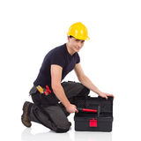 Repairman opening toolbox. Manual worker kneeling on a floor, opening toolbox and looking at camera. Full length studio shot isolated on white Stock Image