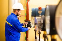 Repairman opens gate valve on pipeline. Measurements manometers and technician man on power plant. Industrial gas and oil refinery royalty free stock images