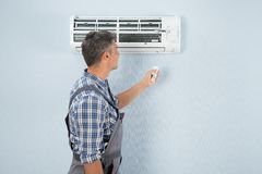 Repairman operating air conditioner with remote controller Stock Images
