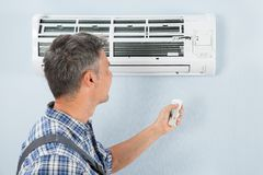 Repairman operating air conditioner with remote controller Stock Image