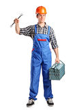 Repairman in overall holding a toolbox and wrench Royalty Free Stock Photography