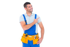 Repairman in overalls pointing on white background. Smiling repairman in overalls wearing tool belt while pointing on white background Royalty Free Stock Photos
