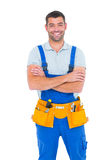 Repairman in overalls wearing tool belt standing arms crossed. Portrait of happy repairman in overalls wearing tool belt standing arms crossed on white Royalty Free Stock Photos