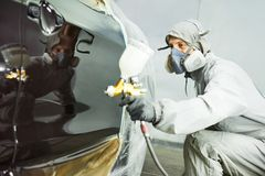 Repairman painter in chamber painting automobile car bonnet. Auto repairman mechanic painter in protective workwear and respirator painting car body bonnet in Royalty Free Stock Images