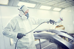 Repairman painter in chamber painting automobile car bumper. Auto repairman mechanic painter in protective workwear and respirator painting car body bumper in Stock Photography