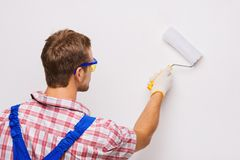 Repairman painting wall by roller Stock Photo