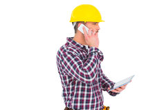 Repairman on the phone holding tablet pc Stock Images