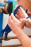 Repairman with pipe wrench. Repairman turning valve with special pipe wrench Stock Photos