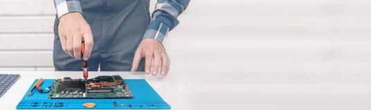 Repairman pracuje w pomocy technicznej, anga?uje w czy?ci? laptop i przywr?ceniu zdjęcie stock