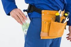 Repairman putting euro notes in pocket Stock Photos