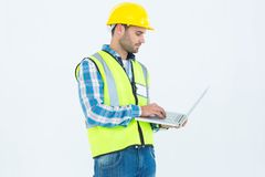 Repairman in reflective workwear using laptop Stock Photo