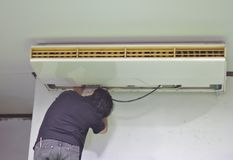 The repairman is repairing the air conditioner on the ceiling. Open the air conditioning cover behind the white wall background in royalty free stock images