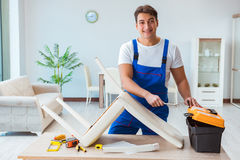 The repairman repairing broken chair at home Stock Photos