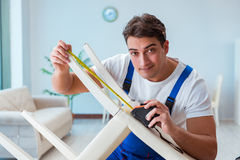 The repairman repairing broken chair at home Royalty Free Stock Photography