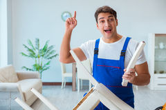 The repairman repairing broken chair at home Royalty Free Stock Images