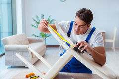 The repairman repairing broken chair at home Stock Images