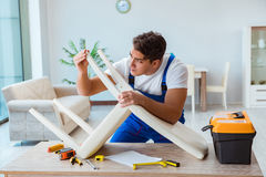 The repairman repairing broken chair at home Royalty Free Stock Photography