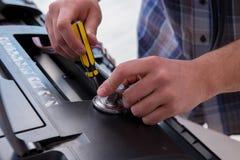 The repairman repairing broken color printer Royalty Free Stock Images