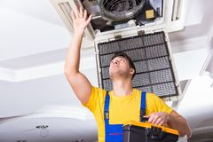 The repairman repairing ceiling air conditioning unit. Repairman repairing ceiling air conditioning unit Royalty Free Stock Image