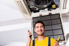 The repairman repairing ceiling air conditioning unit. Repairman repairing ceiling air conditioning unit Stock Photography