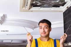 The repairman repairing ceiling air conditioning unit. Repairman repairing ceiling air conditioning unit Royalty Free Stock Photos